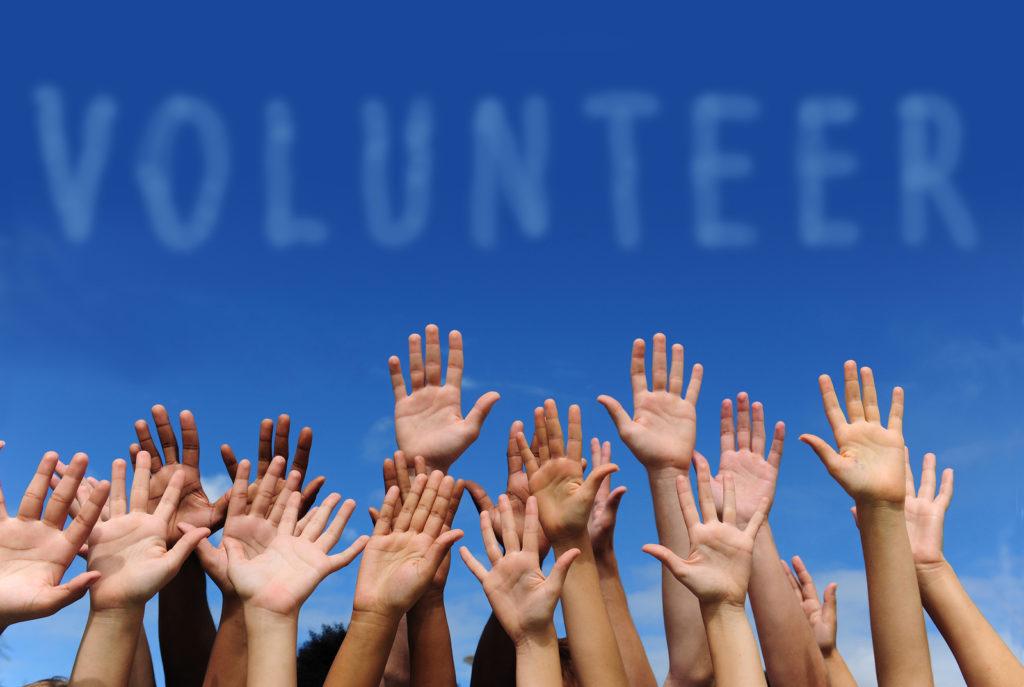 volunteer-group-raising-hands